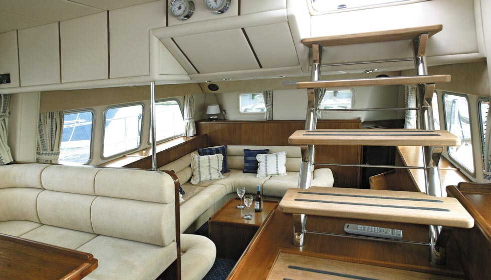 Looking aft from the helm position, showing the two seating/dining areas plus stairway to the flybridge