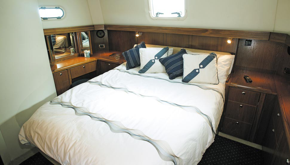The owner's cabin features a full-sized double berth with easy access from both sides, and plenty of clothes storage. The photo shows a teak interior